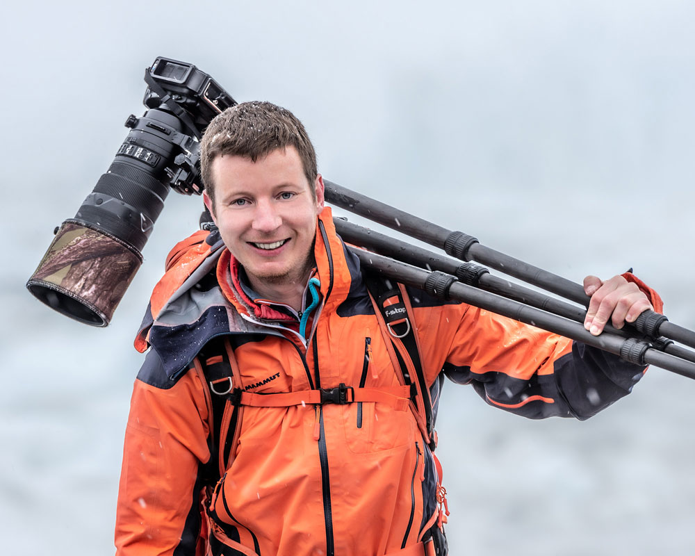 James Rushforth holding a camera on a tripod over his shoulder