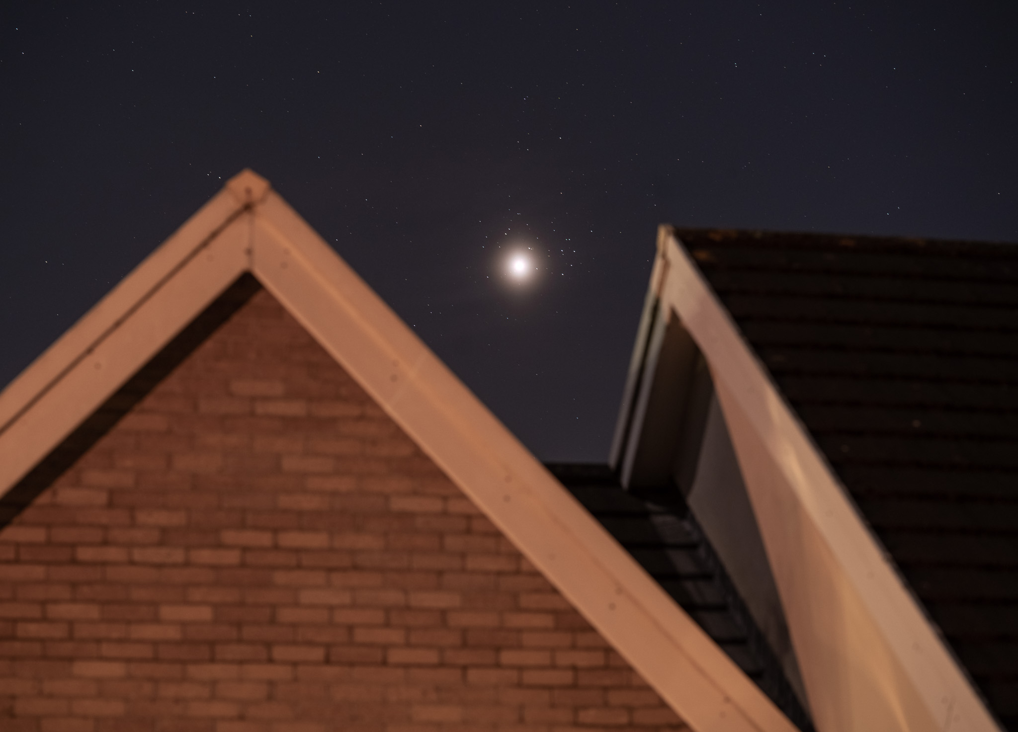 venus and pleiades above rooftops