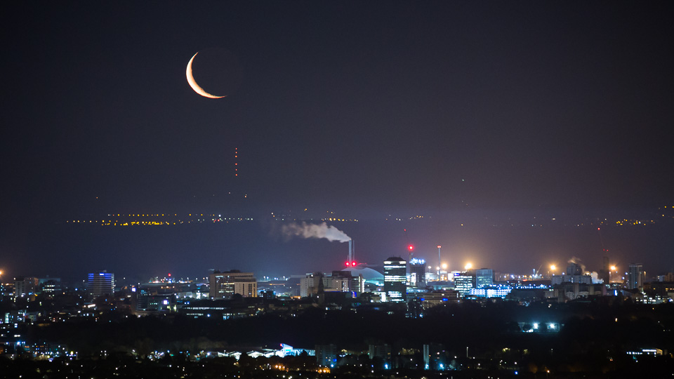 moon over a city landscape at night