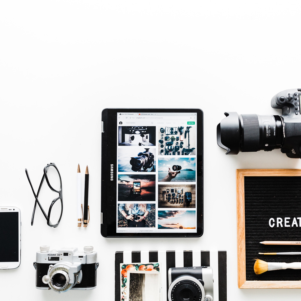 flat lay of camera, phone and tablet