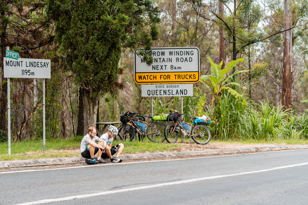 cyclists sat on the curb at the Queensland border