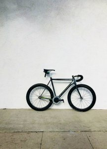 black bicycle against a light grey wall