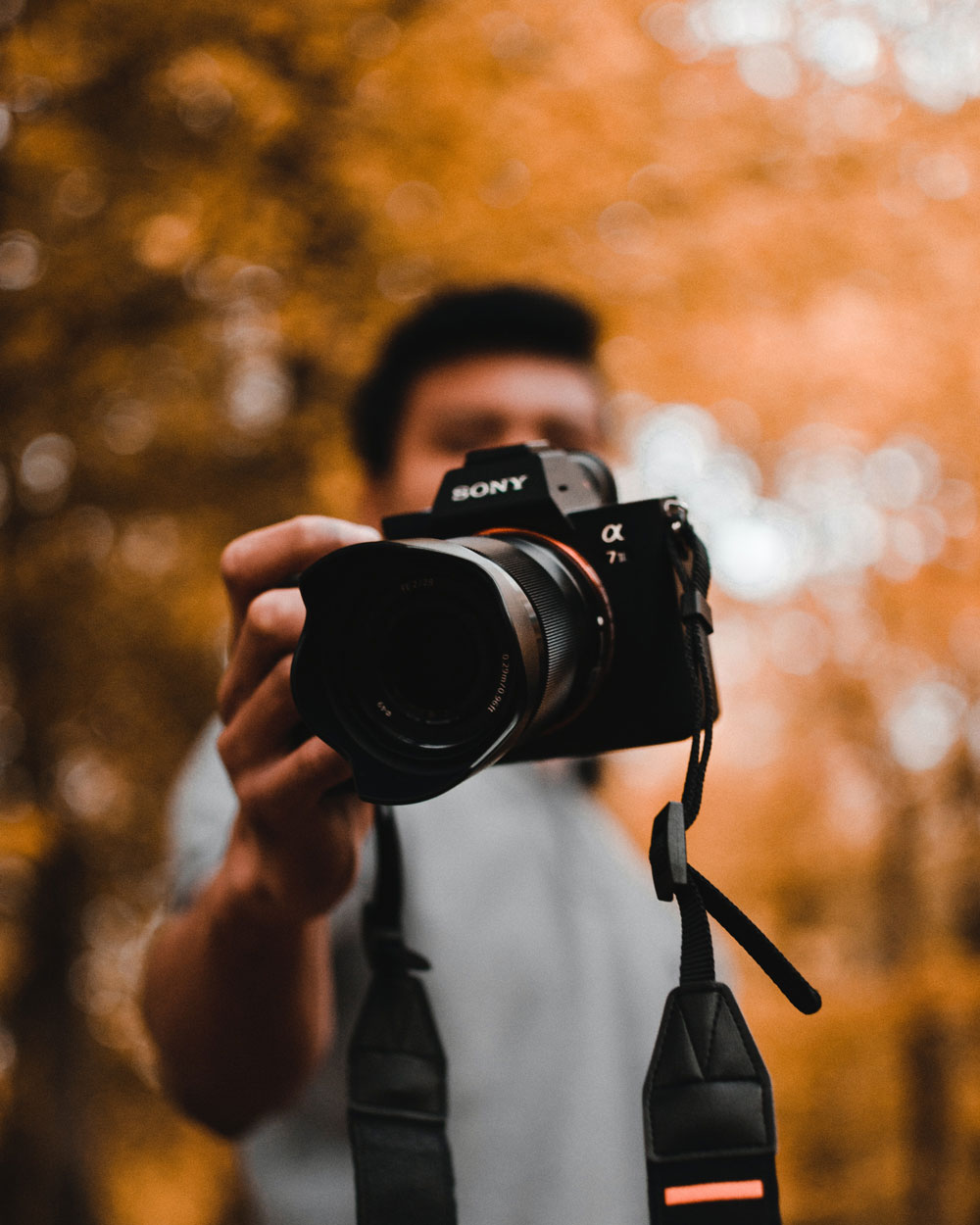 out of focus orange autumnal background, guy holding camera towards the lens covering his face