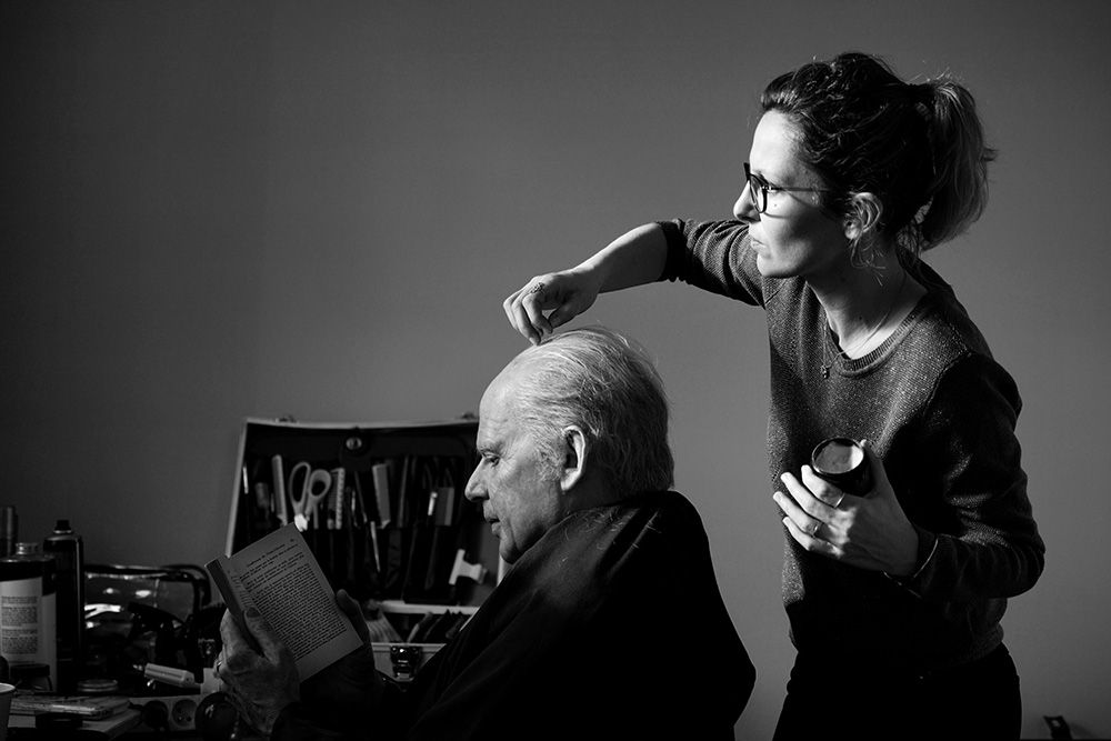 male actor reading his lines while having his hair combed by a woman
